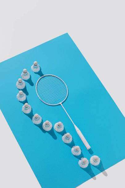 high angle view of badminton racket and shuttlecocks on blue paper, isolated on white - Photo, Image