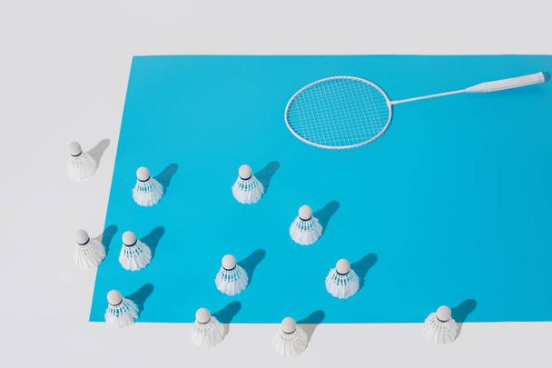 high angle view of white badminton racket and shuttlecocks on blue paper - Photo, Image