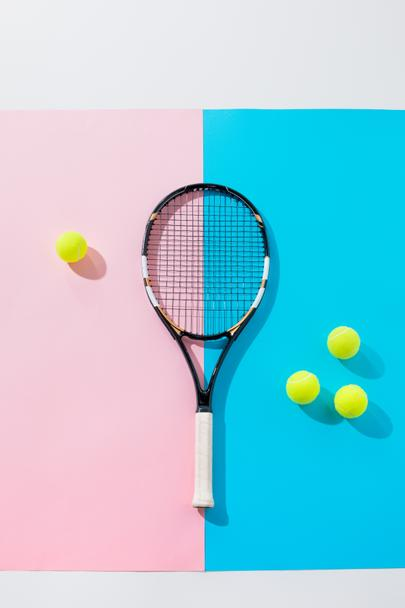 top view of tennis racket and yellow balls on blue and pink papers - Photo, Image