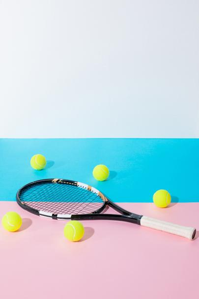 tennis racket and yellow balls on blue and pink papers with copy space - Photo, Image