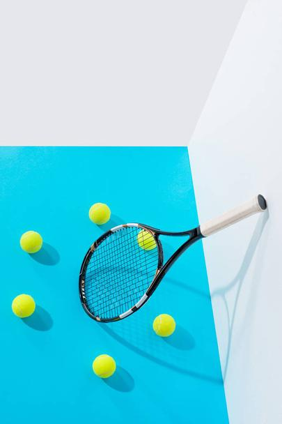 high angle view circle of tennis balls around tennis racket on blue at white wall  - Photo, Image