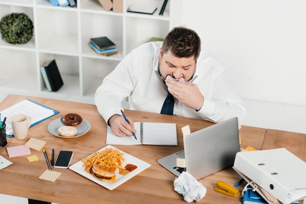 túlsúlyos üzletember, enni donuts, hamburger és sült krumpli, miközben \m/ hivatalban - Fotó, kép