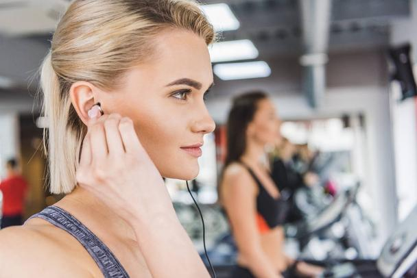 close-up portrait of young beautiful woman listening music with earphones at gym - Photo, Image