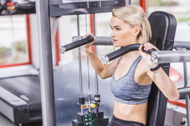 young beautiful woman working out with gym machine - Photo, Image