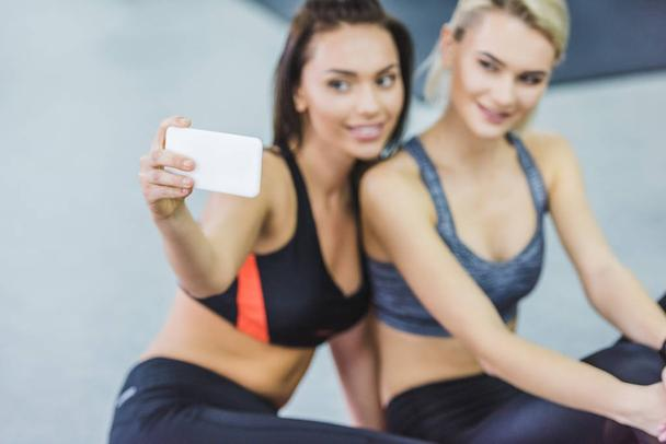 close-up shot of young sportive women taking selfie at gym - Photo, Image