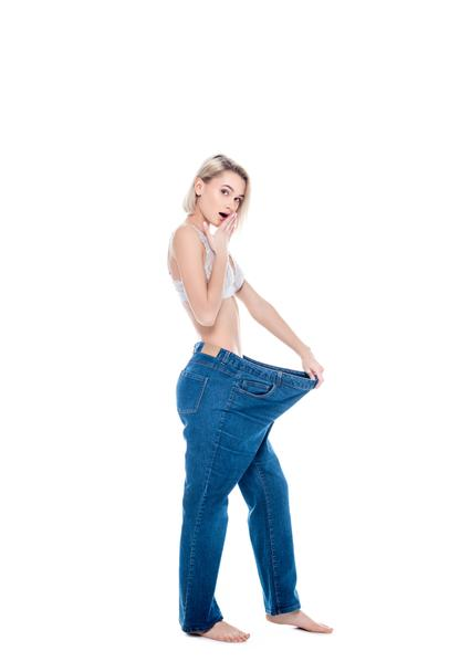 shocked slim girl in old jeans old jeans after losing weight, isolated on white - Photo, Image