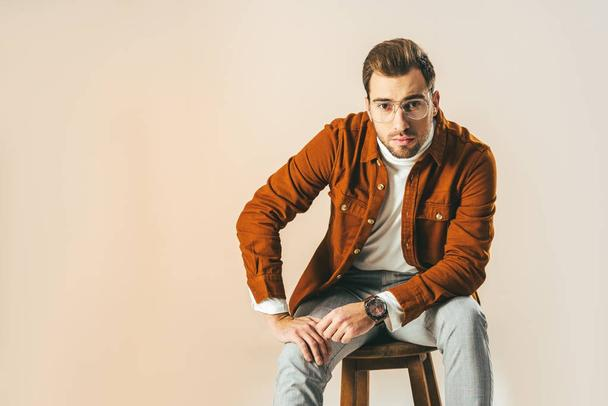 portrait of stylish man in eyeglasses sitting on wooden chair isolated on beige - Photo, Image