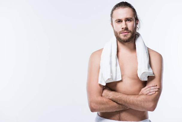 Cheerful caucasian man with bath towel around his neck looking at camera with arms crossed, isolated on white - Photo, Image