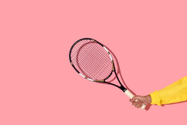 Close-up view of male hand holding tennis racket on pink background  - Photo, Image
