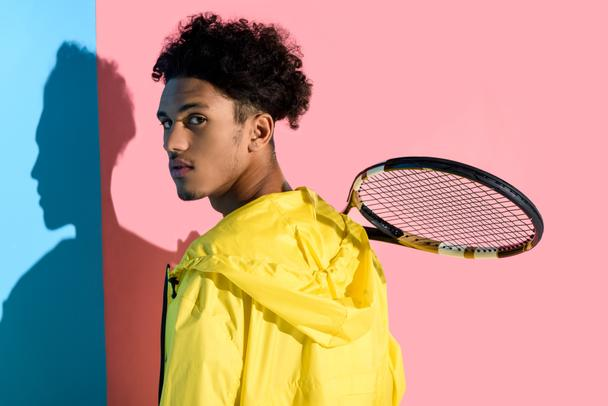 Young bright african american guy holding tennis racket on shoulder on pink and blue background  - Photo, Image