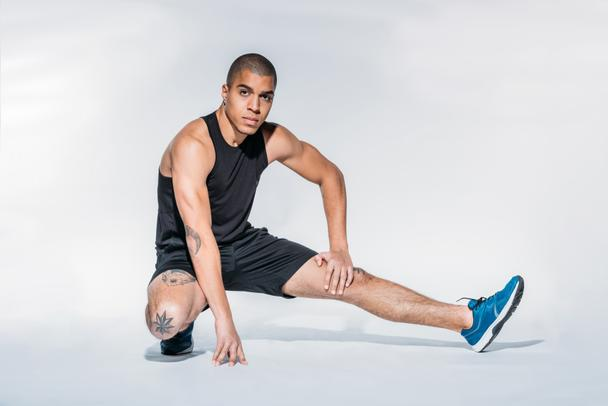 african american sportsman stretching legs and looking at camera - Photo, Image