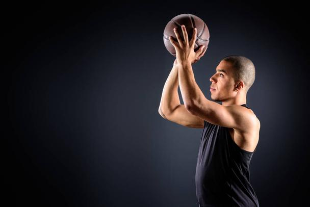 side view of african american basketball player throwing ball on black - Photo, Image