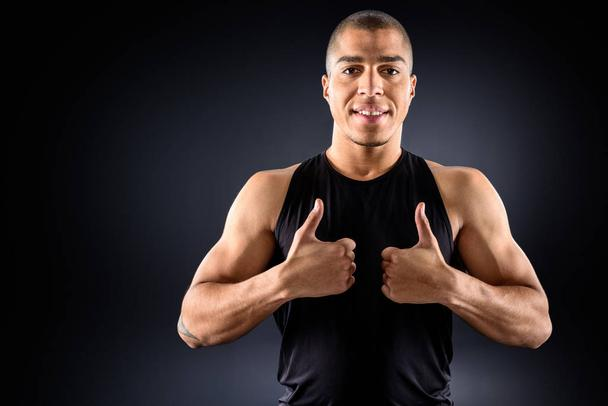 happy african american sportsman showing thumbs up on black - Photo, Image