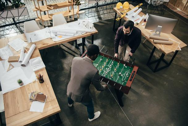 high angle view of young architects playing table football in office full of building plans - Photo, Image