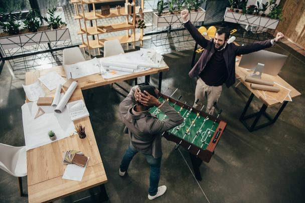 high angle view of young architects playing table football in office - Photo, Image
