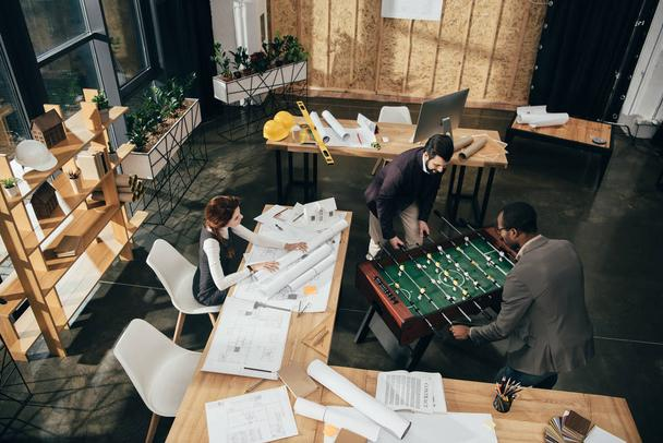 high angle view of young architects playing table football at modern office - Photo, Image