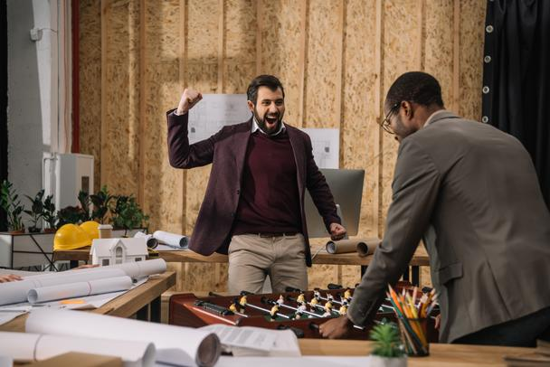 young architects playing table football in office - Photo, Image