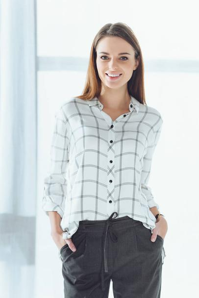 smiling businesswoman standing and looking at camera - Photo, Image