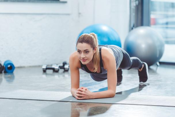 sporty young woman doing plank exercise on yoga mat - Photo, Image