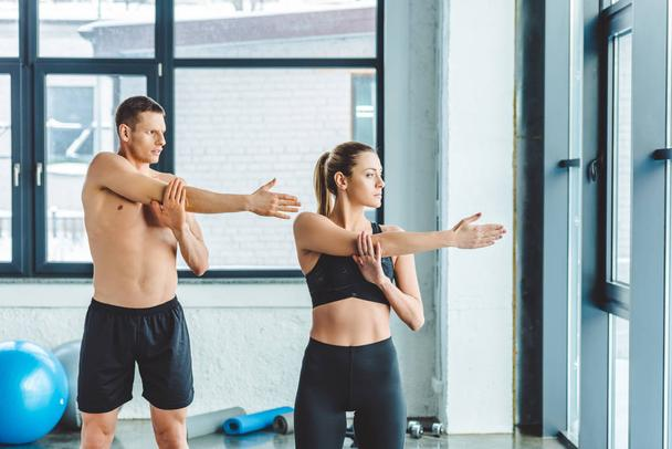 young couple stretching before workout in gym - Photo, Image