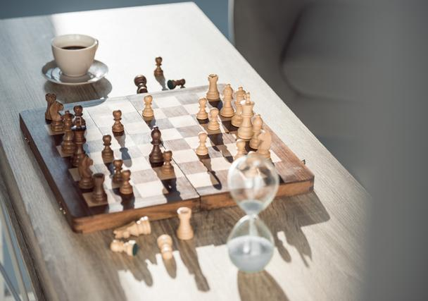 selective focus of chess board with pieces, cup of coffee and sand clock on table  - Photo, Image