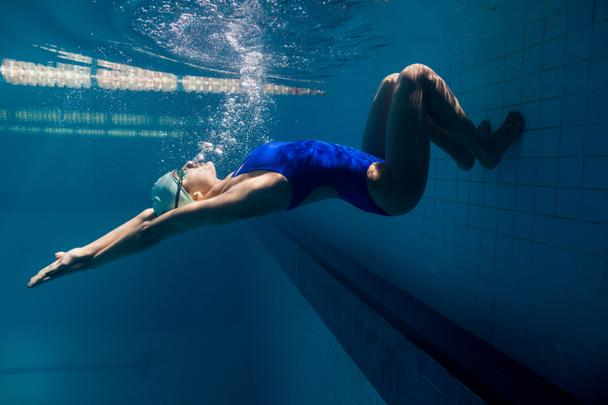 underwater picture of young female swimmer exercising in swimming pool - Photo, Image