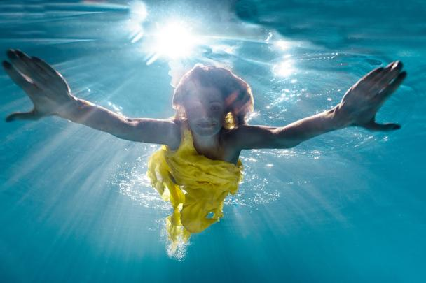 underwater picture of beautiful young woman in dress swimming in swimming pool - Photo, Image