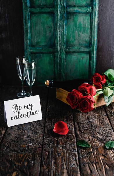 Be my valentine greeting card, red roses and champagne bottle with glasses on shabby table - Photo, Image