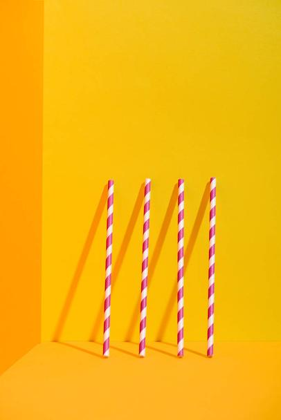 white and red striped straws standing at orange wall - Photo, Image