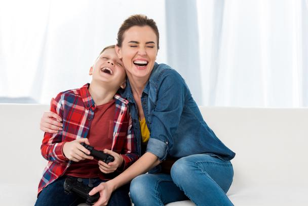 happy mother embracing son while playing video games together - Photo, Image