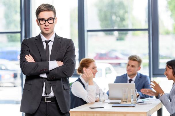 Впевнено бізнесмен перед його колеги в сучасні офісні - Фото, зображення