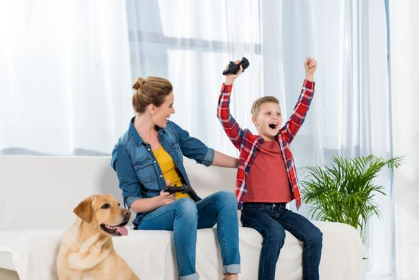 expressive mother and son playing video games while their dog sitting on floor - Photo, Image