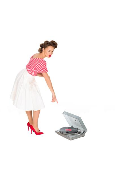 woman in pin up style clothing pointing at phonograph isolated on white - Photo, Image