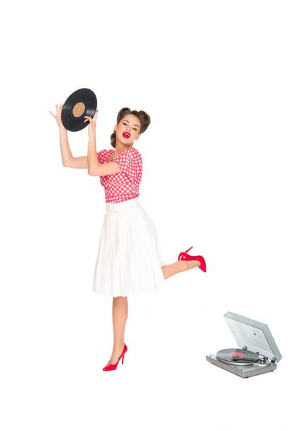 emotional woman in pin up style clothing with vinyl record in hands standing near phonograph isolated on white - Photo, Image
