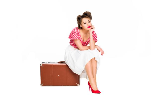 bored beautiful woman in retro clothing sitting on suitcase isolated on white - Photo, Image