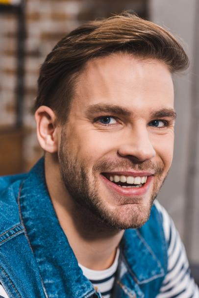 close-up portrait of handsome young man smiling at camera - Photo, Image