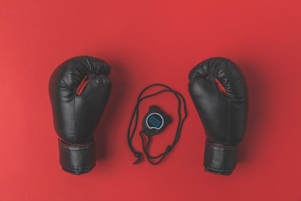 top view of boxing gloves with stopwatch on red tabletop - Photo, Image