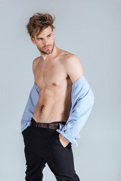 handsome businessman with messy hair taking off his shirt, isolated on grey  - Photo, Image