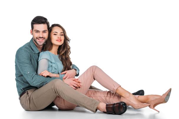 beautiful happy couple sitting on floor on white - Photo, Image