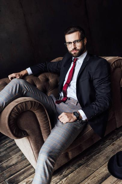 handsome businessman in stylish suit posing on armchair - Photo, Image