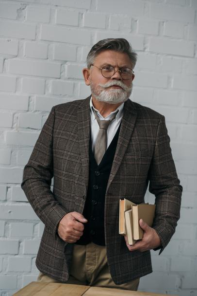 stylish senior man in tweed suit with stack of books - Photo, Image