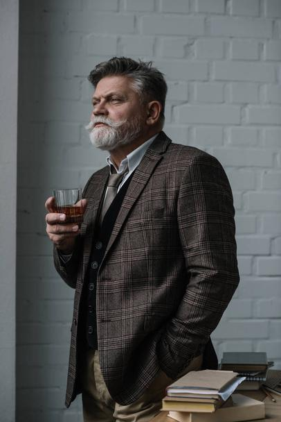 senior man in tweed suit with glass of whiskey looking away - Photo, Image