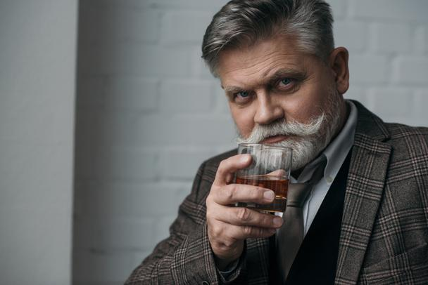 close-up portrait of senior man in tweed suit with glass of whiskey - Photo, Image