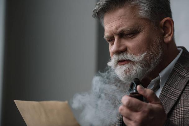 bearded senior man smoking pipe and reading letter - Photo, Image