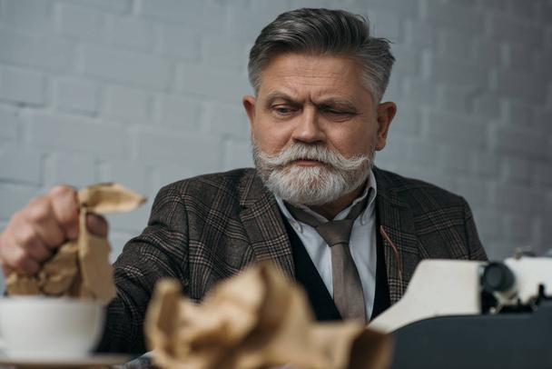 depressed senior writer crumpling paper at workplace - Photo, Image