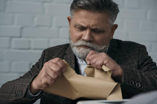close-up portrait of disappointed senior writer tearing his manuscript - Photo, Image