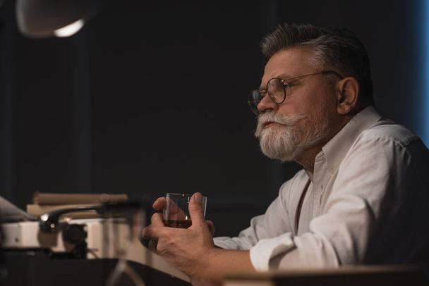 thoughtful senior writer sitting at workplace with glass of whiskey isolated on black - Photo, Image