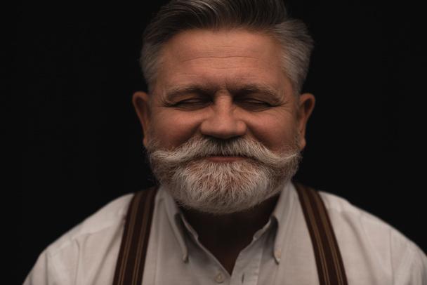 smiling bearded senior man isolated on black - Photo, Image