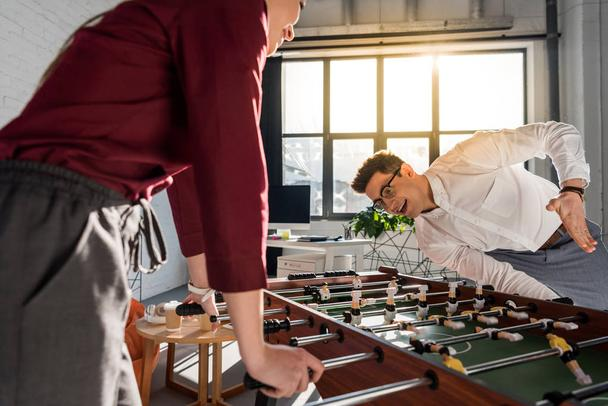 happy colleagues playing table football at modern office - Photo, Image