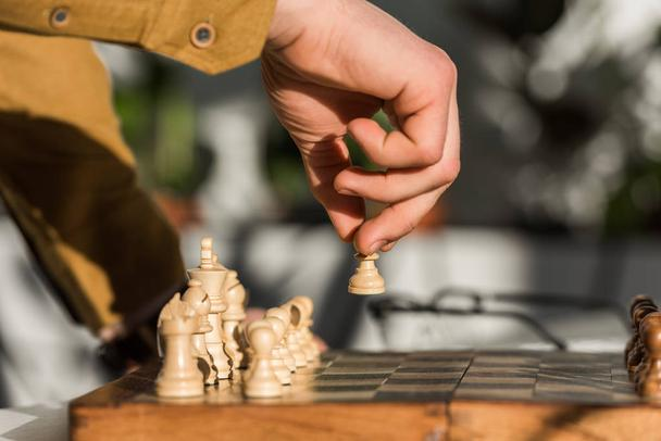 cropped shot of man making move while playing chess - Photo, Image